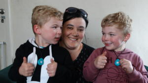 Dunedin twin 4-year old boys who are autistic wearing their Wander Search pendant devices (aid to location if they go missing). The boys are sitting on their mum, who is more confident that if her lads do go missing, they have the devices on them making a search to locate them much faster. Photo credit The Sun, Dunedin