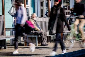 Older man sitting on a bench on the waterfront in Wellington, NZ people are busy walking by. He looks sad and confused, he is lost and can't remember his way home, but he isn't asking for help from passes by either. Photo NZ Police